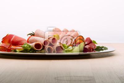 Fototapeta Taca jedzenie pyszne salami, kawałki plasterki szynki, kiełbasy, pomidorów, sałatka i warzyw - talerz mięsa z wyboru