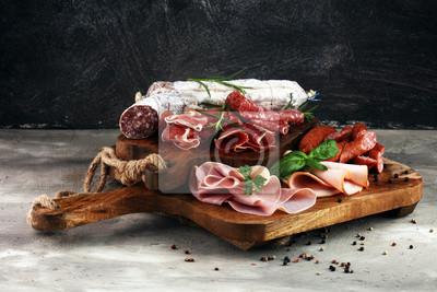 Tacka na jedzenie z pysznym salami, szynką, świeżymi kiełbaskami i ziołami. Talerz mięsny z wyborem
