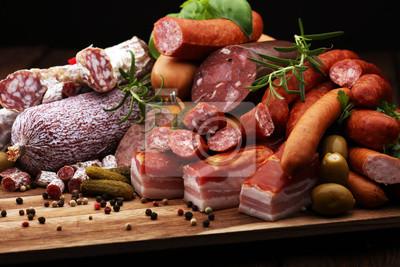 Tacka na jedzenie z pysznym salami, szynką, świeżymi kiełbaskami, ogórkiem i ziołami. Półmisek mięsny
