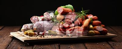 Tacka na jedzenie z pysznym salami, szynką, świeżymi kiełbaskami, ogórkiem i ziołami. Talerz mięsny z wyborem