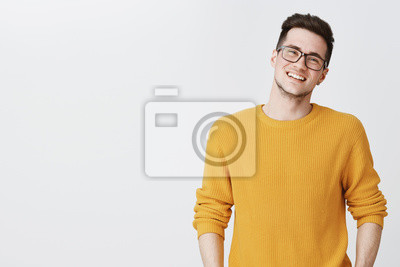 Fototapeta Talia strzał szczęśliwy i zachwycony przystojny młody człowiek w okularach i żółty sweter przechylając głowę, uśmiechając się i śmiejąc się, jak patrząc przyjazny na aparat po prawej stronie miejsca n