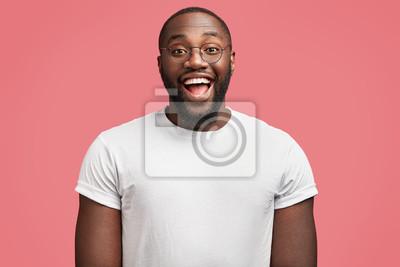 Fototapeta Talia w górę portret cieszy się ciemnoskórych przystojny mężczyzna model z radosnym wyrazem, nosi okrągłe okulary, będąc w dobrym nastroju jako premii od otrzymania za rzetelną pracę, samodzielnie na