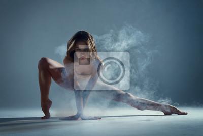 Fototapeta Taniec w chmurze koncepcji. Mięśni brunetki piękna żeńska dziewczyna dorosła kobieta tancerz atleta w mgła dymu dymie jest ubranym taniec body robi seksownego tana elementu występowi na odosobnionym s
