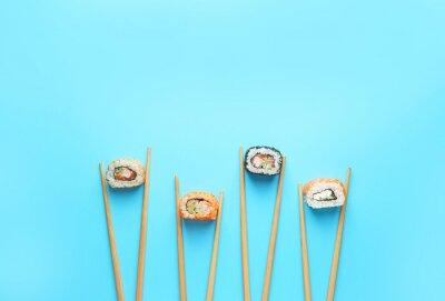 Fototapeta Tasty sushi rolls and chopsticks on color background