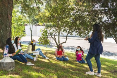 Fototapeta Teacher teaching outdoor classes to a group of Latina teenage students wearing a mask and social distancing due to the coronavirus pandemic
