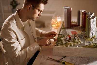 Fototapeta Technology , young man working with a layout of the future building. close up side view photo.