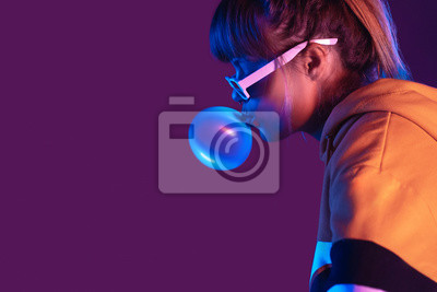 Fototapeta Teen igen girl wear stylish trendy sunglasses and hoodie blowing bubble gum profile side view, pretty young woman fashion cool model with bubblegum 80s at party purple studio background, copy space