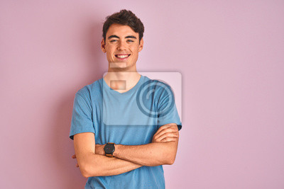 Fototapeta Teenager boy wearing casual t-shirt standing over blue isolated background happy face smiling with crossed arms looking at the camera. Positive person.