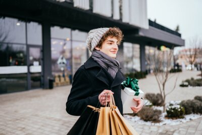 Teenager man with white gift box in coat, knitted hat with shopping bags crowd crossing the street in a city over shopping center.