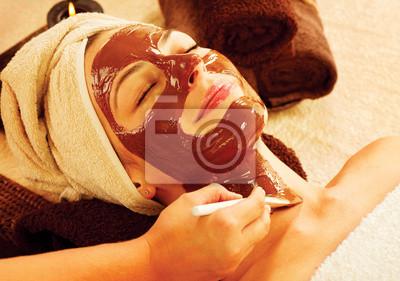 Terapia dla młodej kobiety z czekoladą maską w salonie piękności