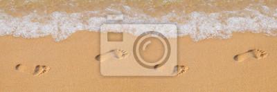 Fototapeta Texture background Footprints of human feet on the sand near the water on the beach