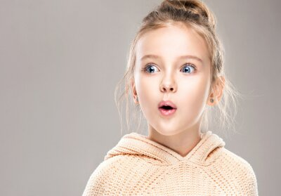 Fototapeta The child is a beautiful girl with wide eyes, look away in surprise. Baby in a knitted sweatshirt . Children's products , clothing and accessories . Expressive facial emotions