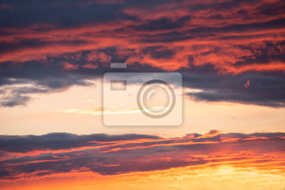 The golden hour of sunset. Orange sky with clouds and yellow sun shining