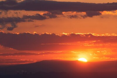 The golden hour of sunset. Orange sky with clouds and yellow sun shining over the mountains.