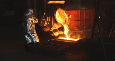 Fototapeta The molten metal is poured into the mold. Melting furnace for cast iron and steel and liquid metal.