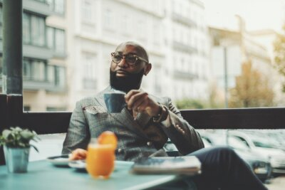 Fototapeta The portrait of a handsome stylish wealthy African guy with a beautiful black beard, in glasses, bald, in an elegant suit, sitting on a rainy morning in a street cafe and drinking delicious coffee