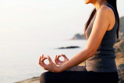Fototapeta The woman meditating in a yoga pose on the tropical beach.