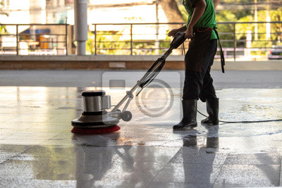 Fototapeta The worker cleaning floor exterior walkway using polishing machine and chemical or acid