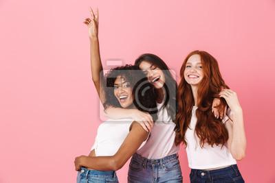 Fototapeta Three cute young girlfriends wearing casual outfits standing
