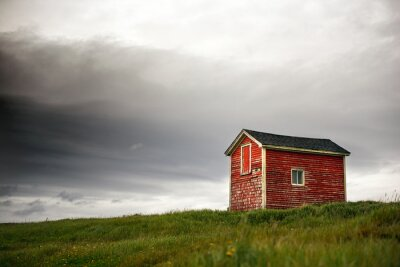 Fototapeta Tiny red building in green grass with dark clouds