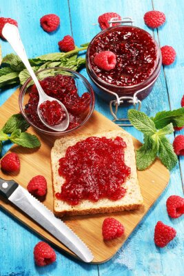 Toast bread with homemade raspberry jam or marmalade on table served with butter for breakfast or brunch
