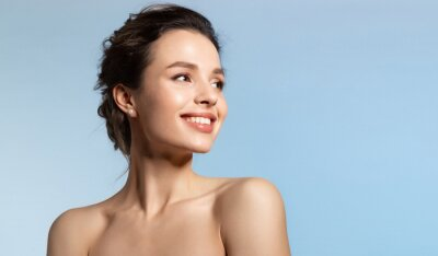 Fototapeta Toothy smiling young woman with shiny glowing perfect facial skin and bare shoulder looking aside.