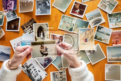 Fototapeta Top view of a senior caucasian woman looking at an old photos themes of memories nostalgia photos retired