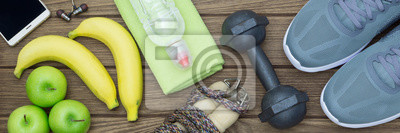 Fototapeta Top view of Healthy lifestyle concept, sport equipments and fresh foods on wood background.  Web Banner.
