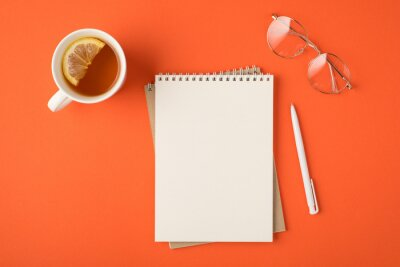 Fototapeta Top view photo of organizer pen glasses and white cup of tea with lemon slice on isolated vivid orange background with empty space