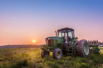 Fototapeta Tractor in a field on a Maryland farm at sunset
