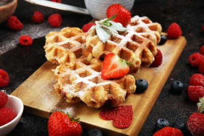 Traditional belgian waffles with fresh blueberries, sugar and raspberries on rustic table