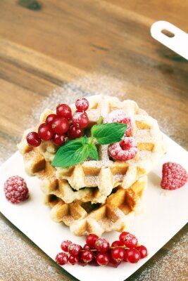 Traditional belgian waffles with fresh mint, sugar and raspberries on table