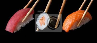 Fototapeta Traditional japanese sushi pieces placed between chopsticks, separated on black background