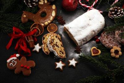 Tradycyjne europejskie świąteczne ciasto, pachnące domowe pieczone, z przyprawami i suszonymi owocami. Pokrojony w stylu rustykalnym stół z gałęzi i ozdób choinkowych xmas