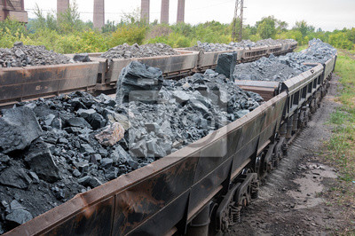 Fototapeta train of tipping cars loaded with raw iron ore at wagon unloading platform of ore dressing factory on industrial background