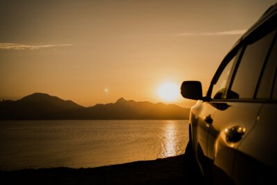 Fototapeta travel tourism by car in the mountains, the sunset, the backdrop of high hills. panoramic view