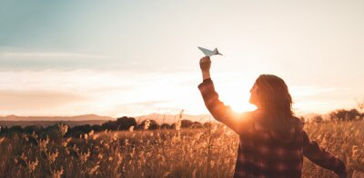 Fototapeta Travelling woman with paper airplane enjoying life and freedom at the land at sunset. Arms outstretched and happiness