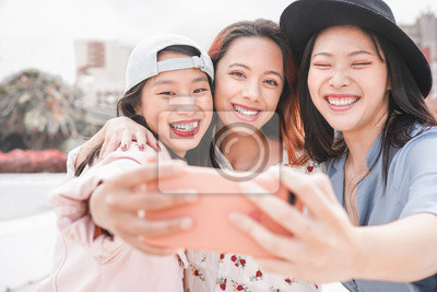 Fototapeta Trendy asian girls making video story for social network app outdoor - Young women friends having fun taking selfie - New technology trends and friendship concept - Focus on faces