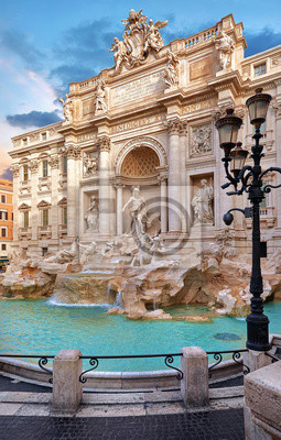 Fototapeta Trevi Fountain in Rome, Italy. Ancient fountain. Roman statues at piazza in old medieval city among traditional italian houses and street lamps. Famous landmark. Touristic destination for vacation.