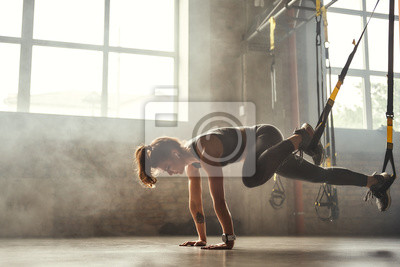 Fototapeta TRX Training. Young athletic woman in sports clothing training legs with trx fitness straps in the gym.