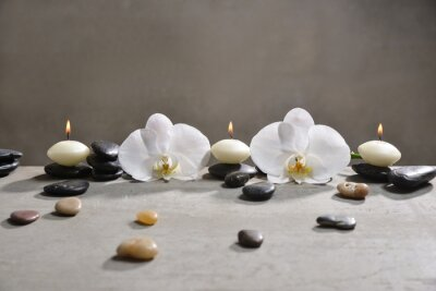 Trzy świeczka z stosem czarni kamienie i biała orchidea na popielatym tle