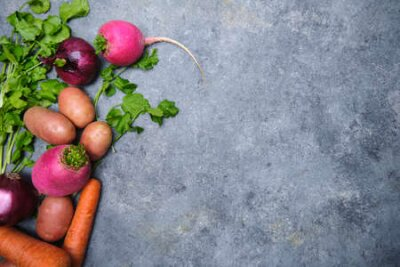 Fototapeta Turnip, cilantro, potatoes, carrots and red onions on a dark background