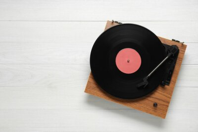 Fototapeta Turntable with vinyl record on white wooden background, top view. Space for text