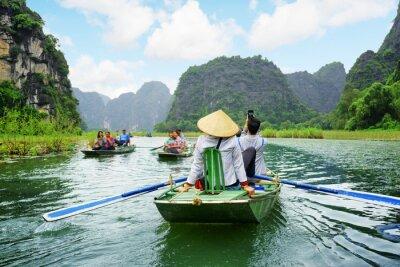 Fototapeta Turyści w łodzi. Wioślarze z użyciem nóg do napędzania wiosła, Wietnam