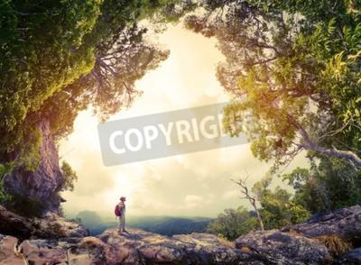 Fototapeta Turysta z plecakiem stojącej na skale otoczonej bujnym lasem tropikalnym