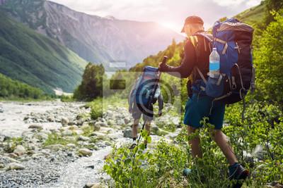 Fototapeta Turystów z plecaki turystyczne na tle pięknej górskiej scenerii. Wspinacze wędrują na wierzchowce. Grupa wycieczkowicze chodzi w górach