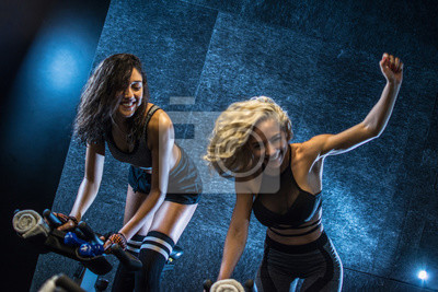Fototapeta Two cheerful young sporty women doing cardio workout on cycling bikes indoors