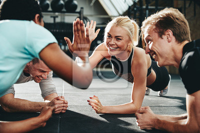 Fototapeta Two friends high fiving while planking on a gym floor
