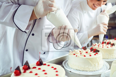 Fototapeta Two pastry chefs decorate a cake from a bag in a pastry shop