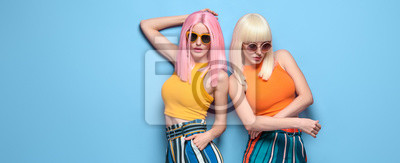 Fototapeta Two Young carefree Woman in stylish sunglasses, striped pants. Beautiful fashionable model girl in trendy summer outfit. Graceful friends with fashion dyed hairstyle, make up on blue. Creative banner